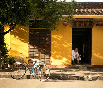 A bicycle outside a yellow house in China