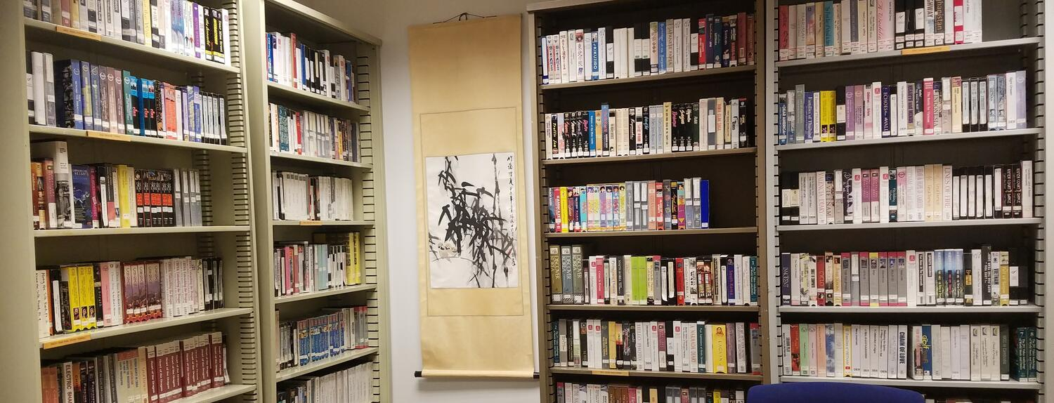 AEMS Library bookshelves with a hanging scroll on the wall.